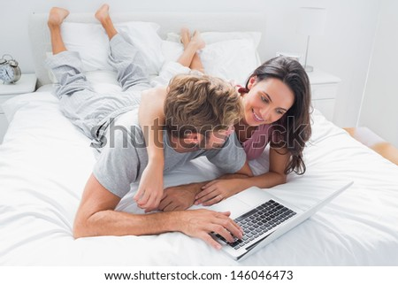 Pretty woman embracing her husband in bed while he is using a laptop - stock photo