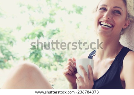 Pretty woman enjoying her morning coffee on a veranda - stock photo