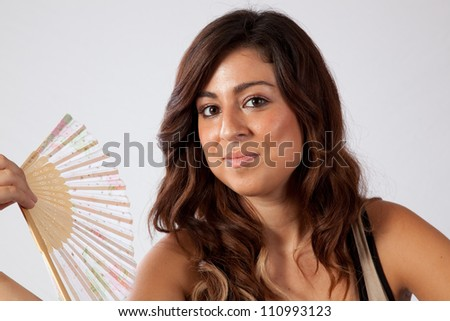 Pretty woman fanning herself with a fan - stock photo