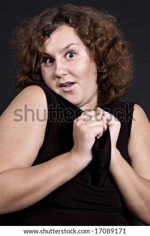 pretty woman gaping in astonishment over dark background - stock photo