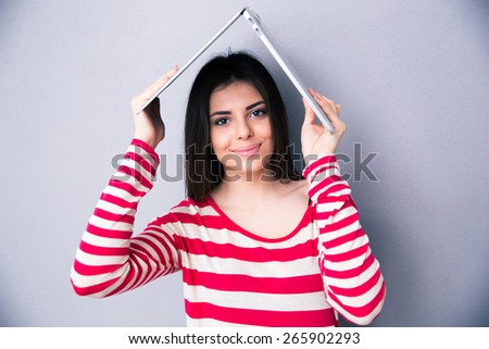 Pretty woman holding a laptop above her head like a roof over gray background. Looking at the camera - stock photo