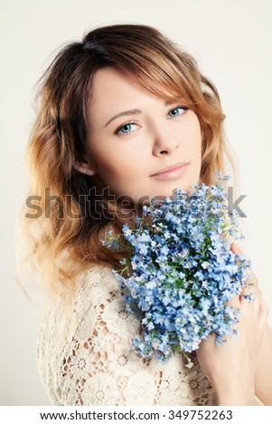 Pretty Woman Holding Blue Flowers - stock photo