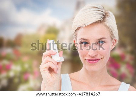 Pretty woman holding inhaler smiling at camera against canal in amsterdam - stock photo