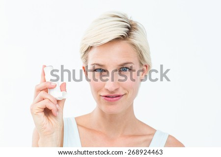 Pretty woman holding inhaler smiling at camera on white background - stock photo