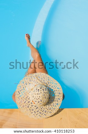 Pretty woman in a hat enjoying a swimming pool at the resort - stock photo