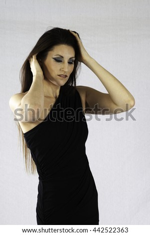 Pretty woman in a little black dress, looking thoughtfully with her hands in her hair  - stock photo