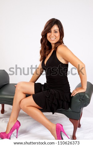 Pretty woman in a little black dress, sitting on a bench with a friendly smile and a sexy pose - stock photo