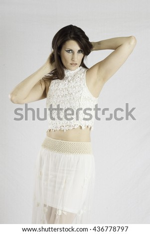 Pretty woman in a white dress,  looking thoughtful while arranging her hair - stock photo