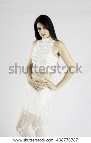 Pretty woman in a white dress,  looking thoughtfully at the camera with her hands on her hip - stock photo