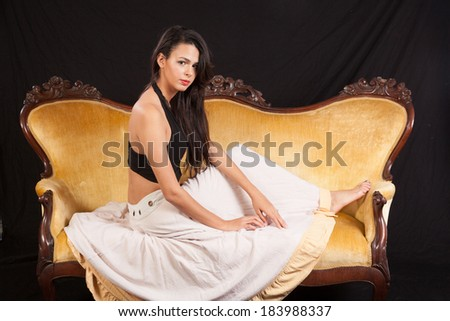 Pretty woman in black top and white skirt, sitting sideways on a gold couch looking at the camera with a serious, friendly and thoughtful expression - stock photo