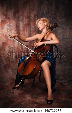Pretty woman in evening dress playing cello - stock photo