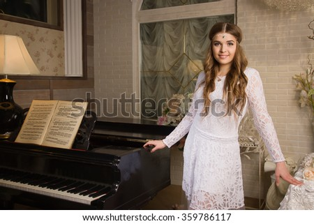Pretty woman in evening dress posing in a vintage interior with a piano - stock photo