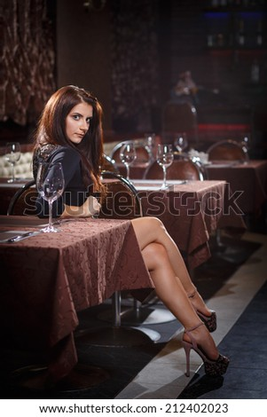 pretty woman in nightclub sitting alone at the table - stock photo