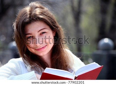 Pretty woman in park reading book and smiling, spring - stock photo