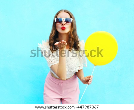 Pretty woman in sunglasses with air balloon sends an air kiss over colorful blue background - stock photo