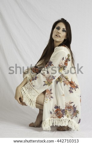 Pretty woman in swim suit and wrap, squatting and  looking thoughtful   - stock photo