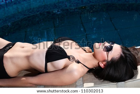 Pretty woman in swimsuit and sunglasses lying on the edge of swimming pool - stock photo