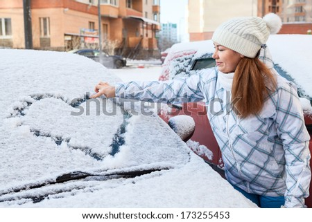 Pretty woman in the winter clothes drawing heart on car - stock photo