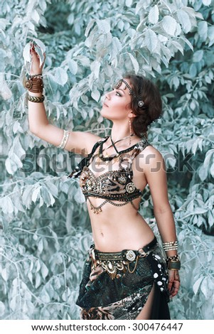 Pretty woman in tribal fusion costume near the beautiful white fairy tree. - stock photo