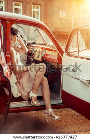 Pretty woman in veil  is sitting in the vintage car. Early summer morning on the background. - stock photo