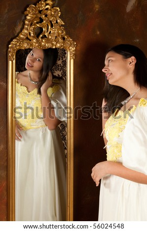 Pretty woman in vintage gown looking into an antique mirror - stock photo