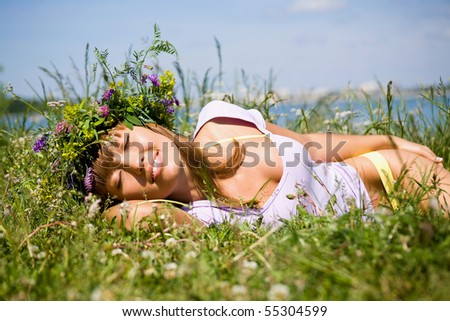 Pretty woman in  wreath of flowers sleep in  meadow on sunny day - stock photo