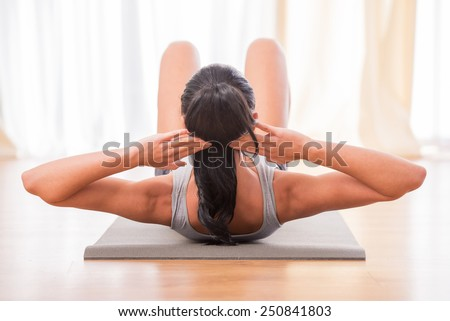 Pretty woman is doing fitness at home on her living room floor. - stock photo