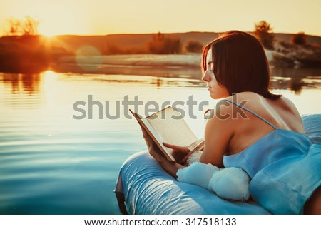 Pretty woman is laying on the floating bed and reading a book. Summer sunset on the background. - stock photo
