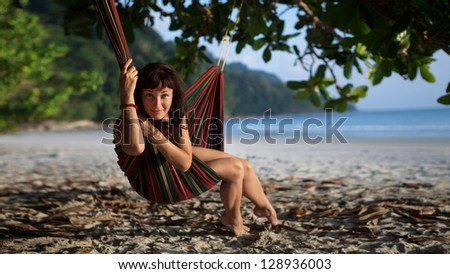 Pretty woman is laying on the hammock on the tropical ocean background. - stock photo
