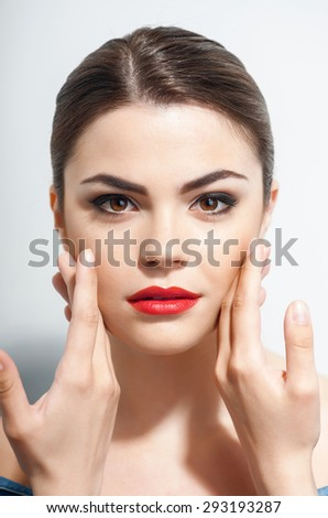 Pretty woman is touching her cheeks with both her hands. She is looking at the camera mysteriously. Isolated on a grey background - stock photo