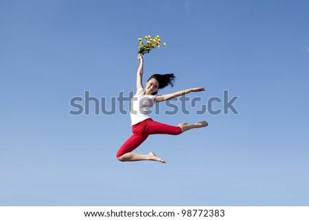 Pretty woman jumping while holding sunflowers. Shot over clear blue sky - stock photo