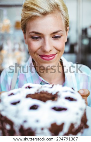 Pretty woman looking at a chocolate cake at the bakery - stock photo