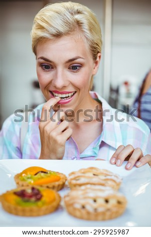 Pretty woman looking at a fruit pie at the bakery - stock photo