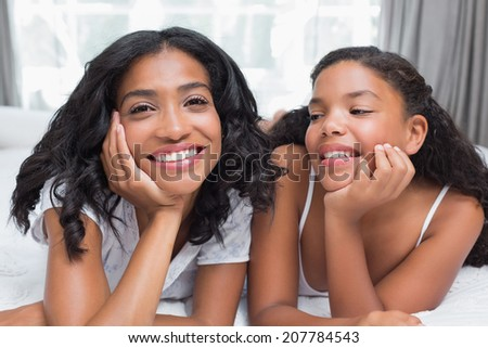 Pretty woman lying on bed with her daughter smiling at camera at home in bedroom - stock photo