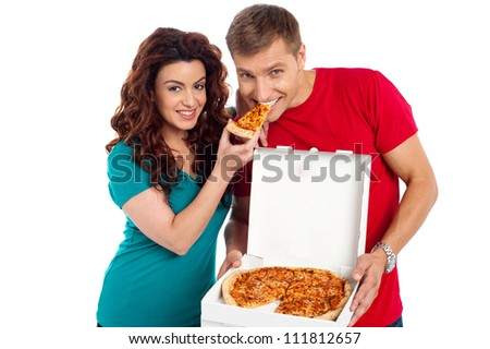 Pretty woman making her boyfriend end pizza piece. Great love and bonding - stock photo