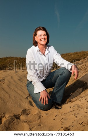 Pretty woman middle aged sitting in sand dune enjoying outdoors. Clear sunny spring day with blue sky. - stock photo