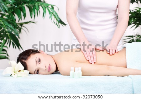 Pretty woman on back massage in spa center - stock photo