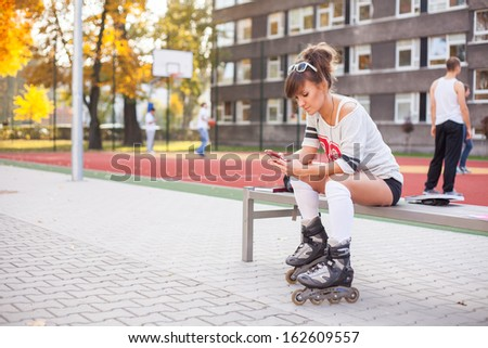 Pretty woman on rollerblades sitting on bench with mobile phone. - stock photo