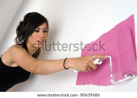 Pretty Woman Paints White Wall Pink Paint Roller Home Improvement Project Homemaker - stock photo