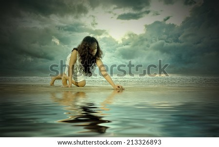 pretty woman performs on the beach - soft cinematic colour effects. digital compositing, colour tone, water reflection and ripple effects. - stock photo