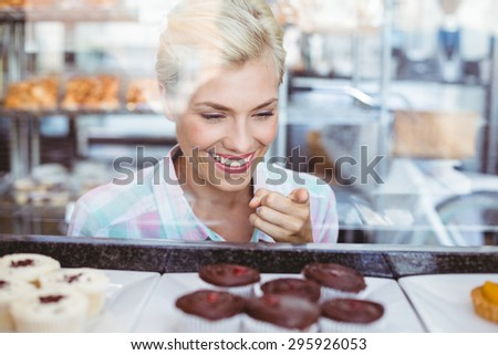 Pretty woman pointing a cup cake at the bakery - stock photo