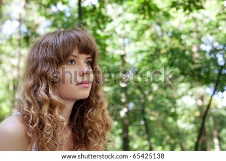 Pretty woman posing in forest - stock photo