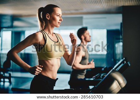 Pretty woman running on treadmill with fit young man on background - stock photo