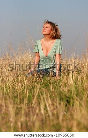 pretty woman seating  field - stock photo
