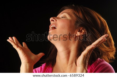 Pretty woman shaking her hair in a moment of ecstasy - stock photo