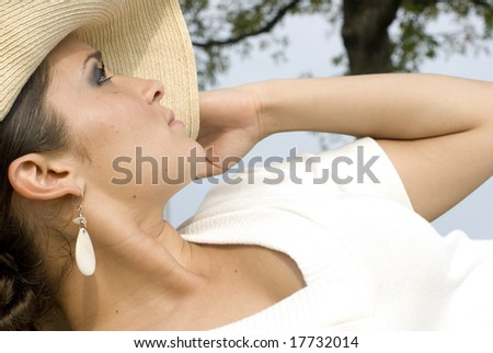 Pretty woman shielding the sun with her cream hat - stock photo
