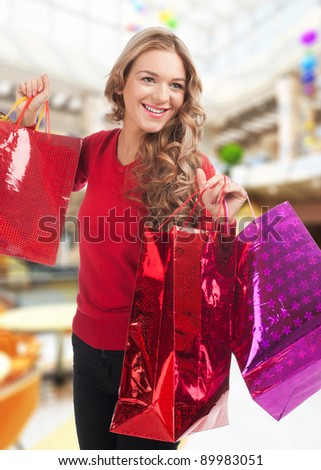 Pretty woman shopping for christmas gifts. Happy young woman with colorful shopping bags. - stock photo