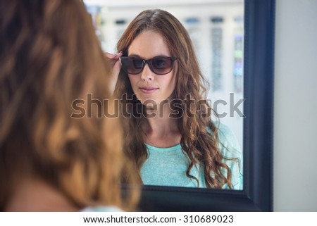 Pretty woman shopping for sunglasses at the optometry store - stock photo