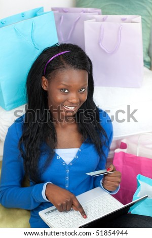Pretty woman shopping on-line in the living-room - stock photo