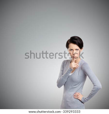 Pretty woman shows shush gesture, isolated on grey background - stock photo